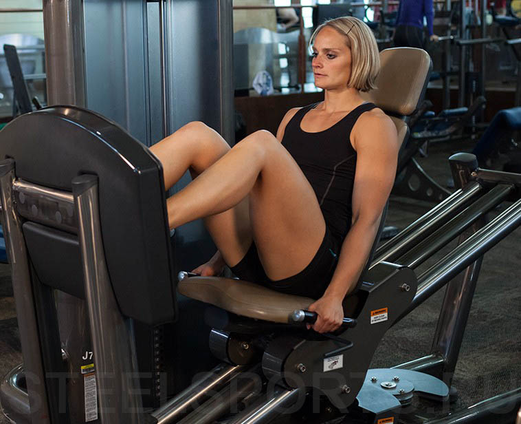 Жим ногами сидя в тренажере в женском исполнении