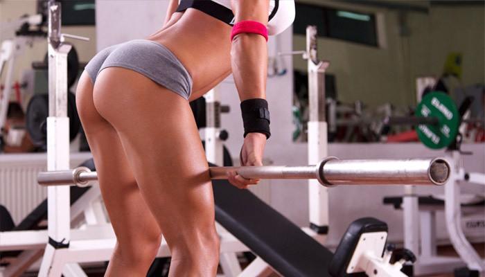 Девушка занимается в тренажерном зале, чтобы похудеть в ногах